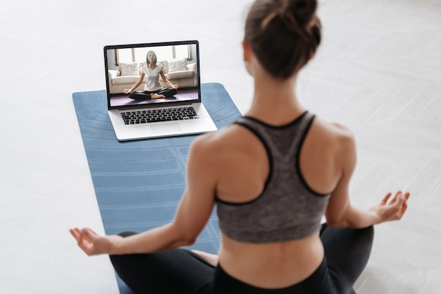 Close up of young sporty woman practicing yoga online with laptop at home
