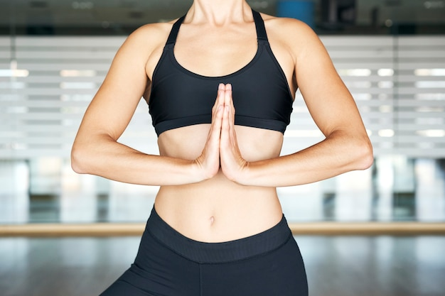 Close up of young sporty yogi woman in gym practicing yoga, pranamasana, wearing black sportswear