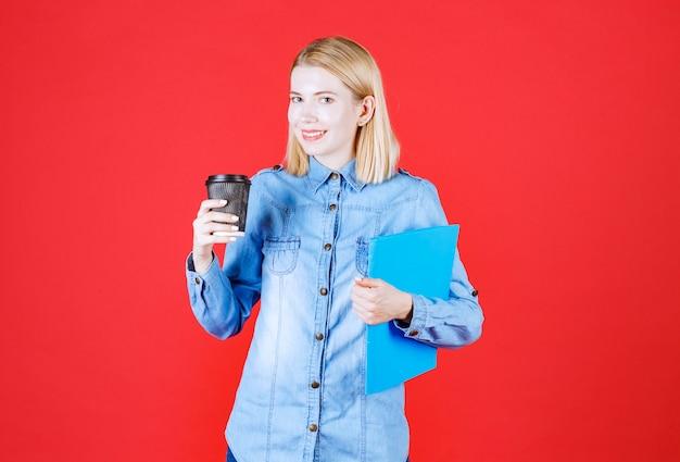 青いドキュメントフォルダを保持し、コーヒーを飲む若い学生の女の子を閉じる