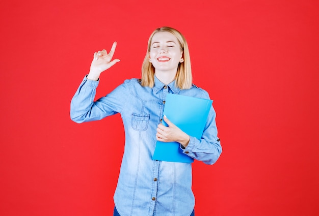 Close up young student girl holding blue document folder and pointing up showing advertisement and closed mouth