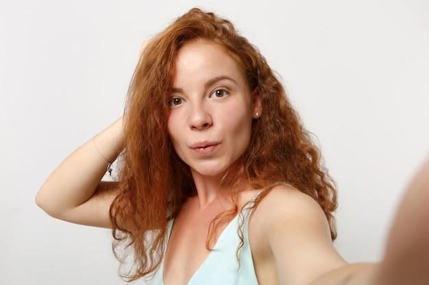 白い背景のスタジオの肖像画に分離されたポーズをとってカジュアルな明るい服を着た若い見事な赤毛の女性の女の子を閉じます。人々のライフスタイルの概念。コピースペースをモックアップします。携帯電話で自撮り写真を撮る。