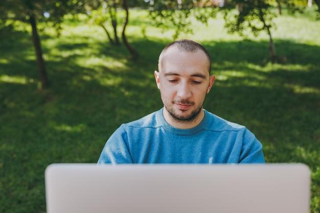 ラップトップを使用して都市公園のテーブルに座って、屋外で作業して、カジュアルな青いシャツを着た若い成功したスマートマンのビジネスマンや学生を閉じます。モバイルオフィスのコンセプト。広告用のスペースをコピーします。