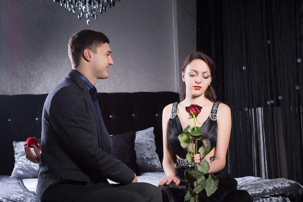 ガールフレンドが赤いバラの花を持っている間、寝室に座って、上品な服を着て、若い恋人を閉じます。
