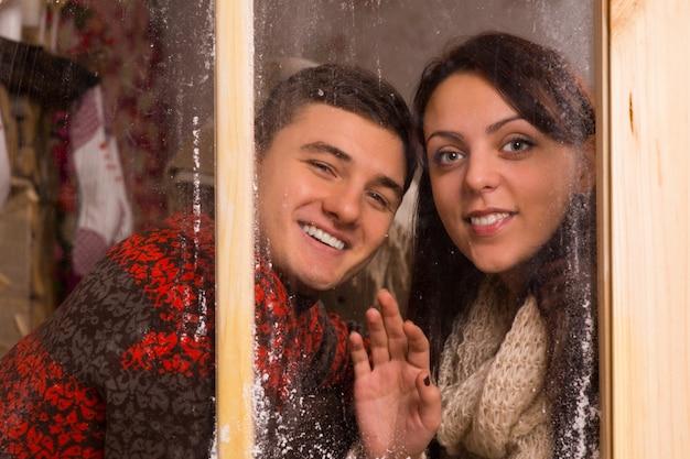 ガラス窓の後ろに笑みを浮かべて、カメラを見て冬の長袖の衣装で若い恋人を閉じます。