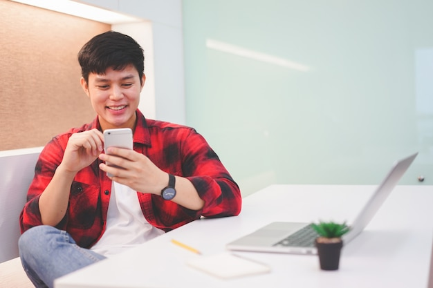 Close up young teenager playing smartphone in private room, millennial lifestyle concept