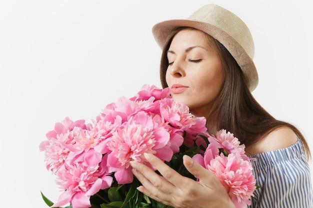 흰색 배경에 격리된 분홍색 모란 꽃다발을 킁킁거리며 드레스 모자를 쓴 젊은 부드러운 여성을 닫습니다. 성 발렌타인 데이 국제 여성의 날 휴일 컨셉입니다. 광고 영역