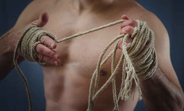 Close-up of a young thai boxer hands hemp ropes are wrapped before the fight or training