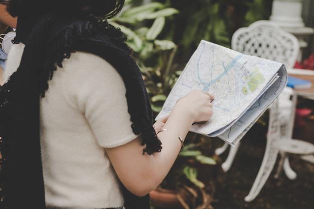 Закрыть молодых туристов, держащих и глядя на карту