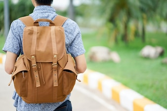 Close up young traveler man carrying backpack for trip concept