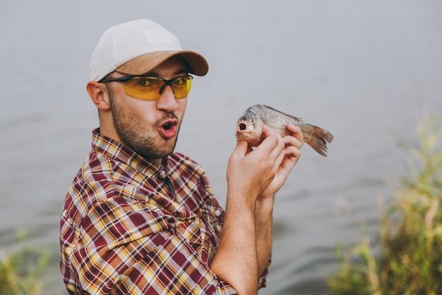 클로즈업 체크무늬 셔츠, 모자, 선글라스를 쓴 면도하지 않은 젊은이는 물고기를 잡고 그것을 보여주고 물 배경에 있는 호수 기슭에서 기뻐합니다. 라이프 스타일, 레크리에이션, 어부의 레저 개념