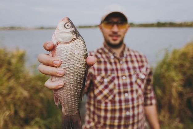 클로즈업 체크무늬 셔츠, 모자, 선글라스를 쓴 면도하지 않은 젊은 남자가 물고기를 잡고 물, 관목, 갈대 배경의 호수 기슭에서 그것을 보여줍니다. 라이프 스타일, 레크리에이션, 어부의 레저 개념