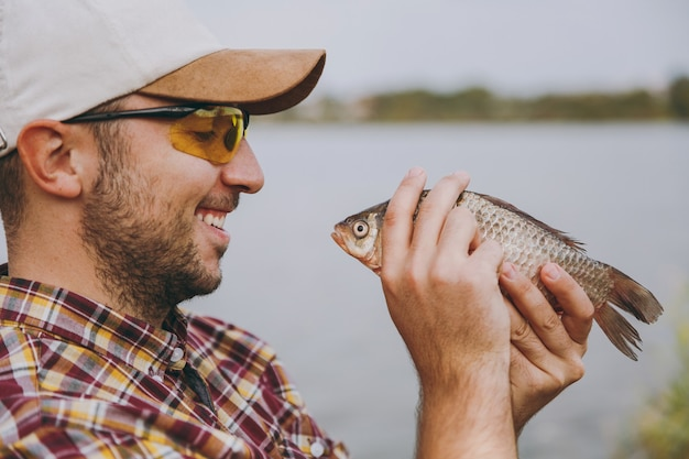Close up young unshaven smiling man in checkered shirt, cap and sunglasses caught a fish and looks at it on the shore of lake on background of water. lifestyle, recreation, fisherman leisure concept