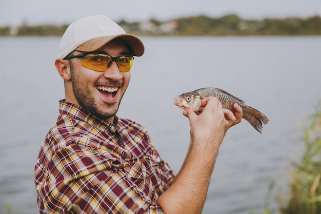 클로즈업 체크무늬 셔츠, 모자, 선글라스를 쓴 면도하지 않은 젊은 남자는 물고기를 잡고 팔에 안고 물 배경의 호수 기슭에서 기뻐합니다. 라이프 스타일, 어부의 레저 개념