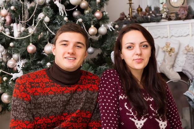 さまざまな装飾品でクリスマスツリーの装飾の前にカジュアルな長袖の冬のシャツの若い白人カップルを閉じます。