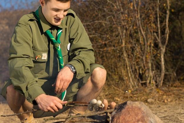 Закройте молодого белого мужчины-разведчика, готовящего сосиски на палаточном лагере примитивным способом.