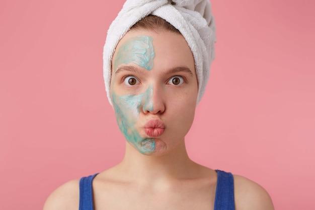 Primo piano di giovane donna dopo la doccia con un asciugamano in testa, con mezza maschera, sguardo sorpreso.