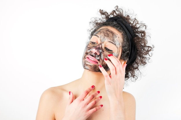 Close-up of a young woman applying black mask against white background