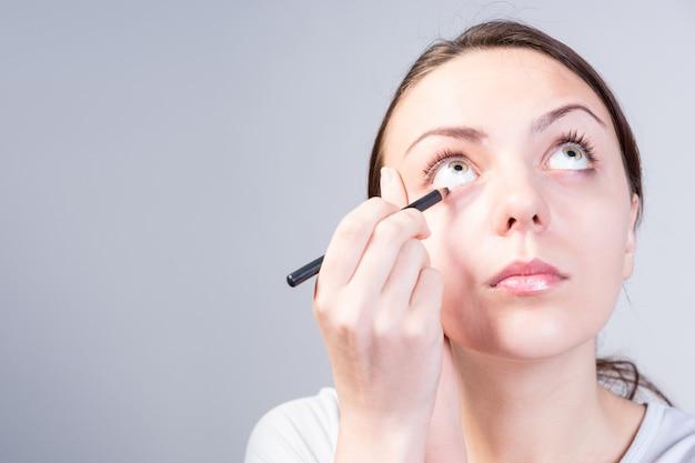 Закройте вверх по молодой женщине, применяя макияж подводки для глаз на ее нижнем веке, серьезно глядя на сером фоне.