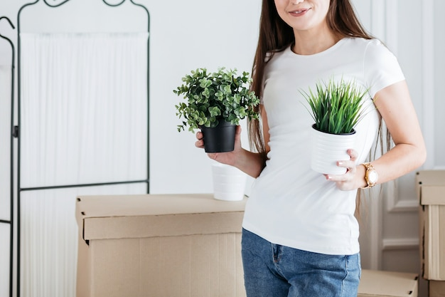 Close up. young woman arranging flower pots in new apartment