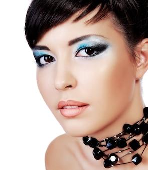 クローズアップの若い女性のスタイリッシュなファッションのアイメイクで美しい顔。