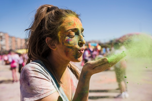 Close-up of a young woman blowing holi color