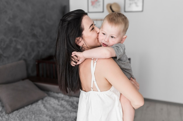 Close-up of young woman carrying her little cute son kissing on his cheeks