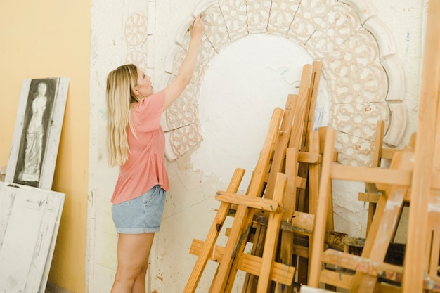Close-up of young woman carving on wall with tools