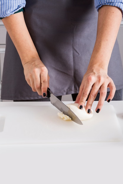 Close-up of a young woman cutting the cheese with knife on chopping board