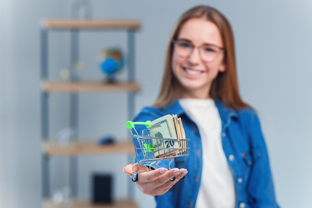 Close up young woman in denim shirt and eyeglasses holds small shopping cart with us dollar.