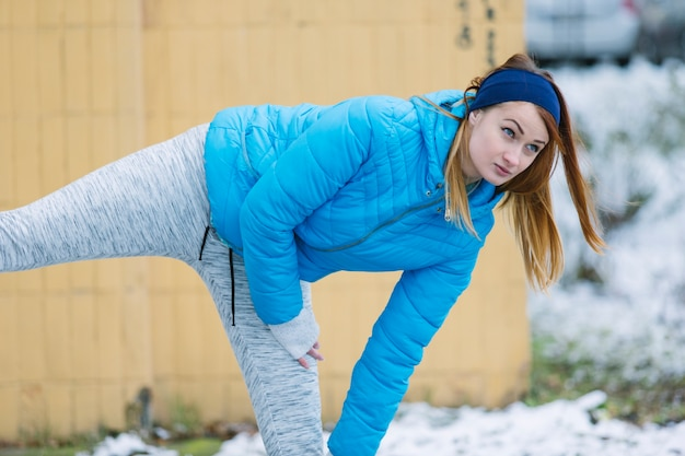 Close-up of young woman doing exercise in winter