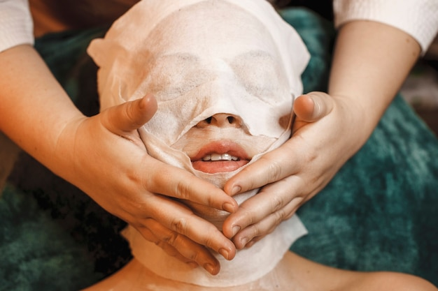 Close up of a young woman doing facial skin care procedures in a wellness spa center.