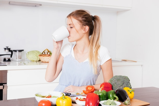 Close-up of a young woman drinking the coffee with fresh colorful vegetables on wooden table