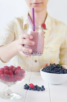 Close up of a young woman drinking a smoothie