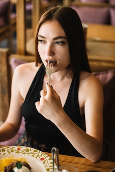 Close-up of young woman eating dessert with fork