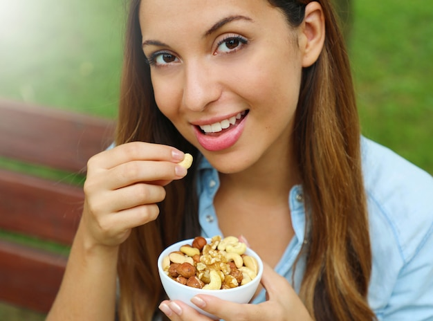 Close up of young woman eating mixed nuts in the park.
