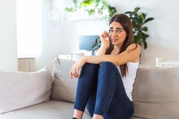 화가 나거나 슬프거나 불행하거나 실망해서 집에서 외롭게 울고 있는 젊은 여성을 닫아라. 정서적 충격과 삶의 문제