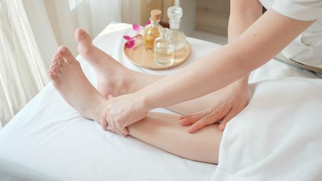 Закройте вверх молодая женщина получая массаж рефлексологии ноги на салоне курорта красоты. массаж для здоровья