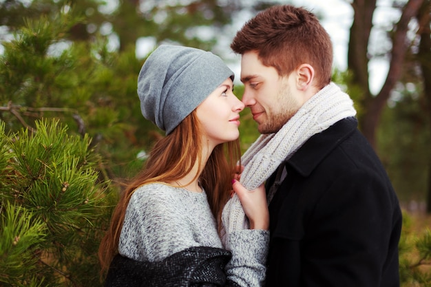 Close-up of young woman grabbing her boyfriend's scarf