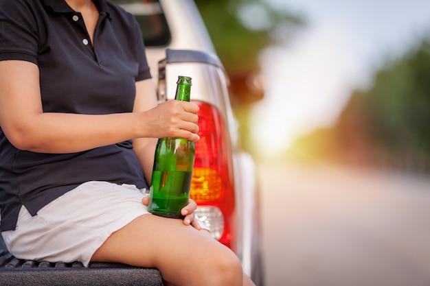 그의 손으로 녹색 병된 맥주를 들고 젊은 여자를 닫습니다