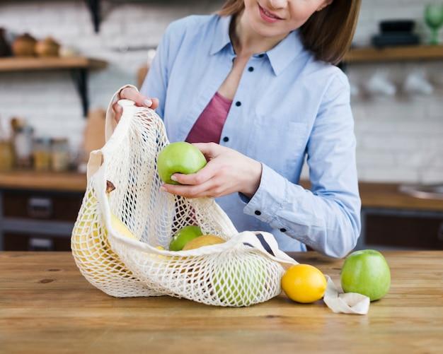 Макро молодая женщина, держащая сумку со свежими фруктами