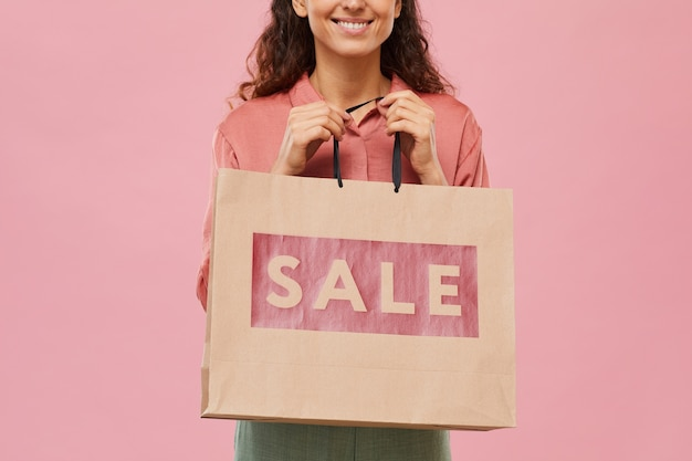 Close-up of young woman holding big sale paper bag in her hands isolated on pink background