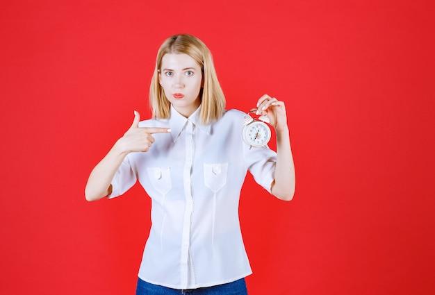 赤い壁に孤立して指している間時計を保持している若い女性を閉じる