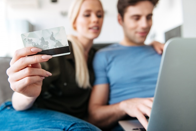 Close up of young woman holding credit card while using laptop with her husband