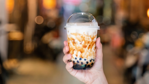 Close up of young woman holding a cup of tapioca pearl bubble milk tea