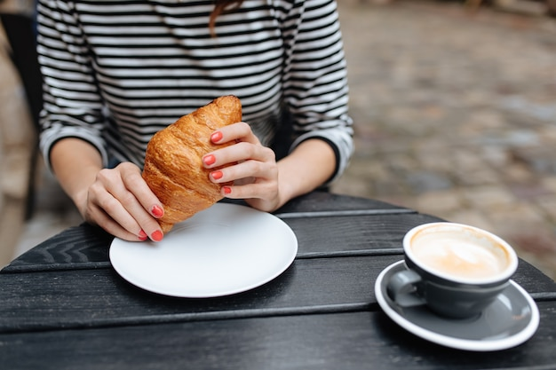 Close up of young woman holding a fresh croissant and tasty capuccino on cafe terrace