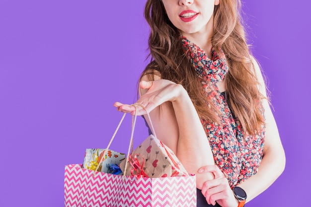Close-up of young woman holding shopping paper bag with wrapped gift boxes