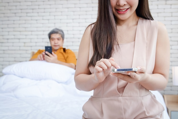 Close-up of a young woman holding a smartphone while chatting online with other men