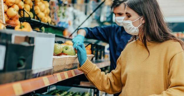Закройте вверх. молодая женщина в защитной маске покупает яблоки