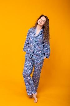 Крупным планом молодая женщина в синей пижаме, изолированные на желтой стене