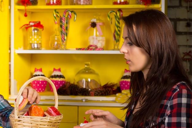 テーブルの上にペストリーでいっぱいのバスケットを持って店に座っている市松模様のシャツを着た若い女性を閉じます。